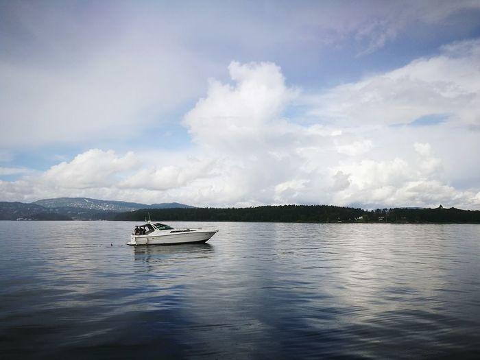 Boat Sailing On Lake Against Sky