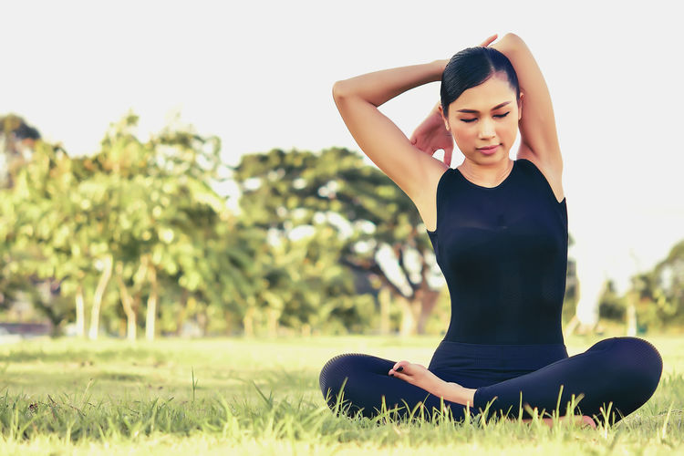 Beautiful women maintain health with yoga exercises. Young Women Young Adult Leisure Activity Exercising Lifestyles One Person Women Grass Healthy Lifestyle Plant Real People Relaxation Exercise Wellbeing Adult Relaxation Focus On Foreground Sport Nature Day Beautiful Woman Outdoors Arms Raised Body Conscious