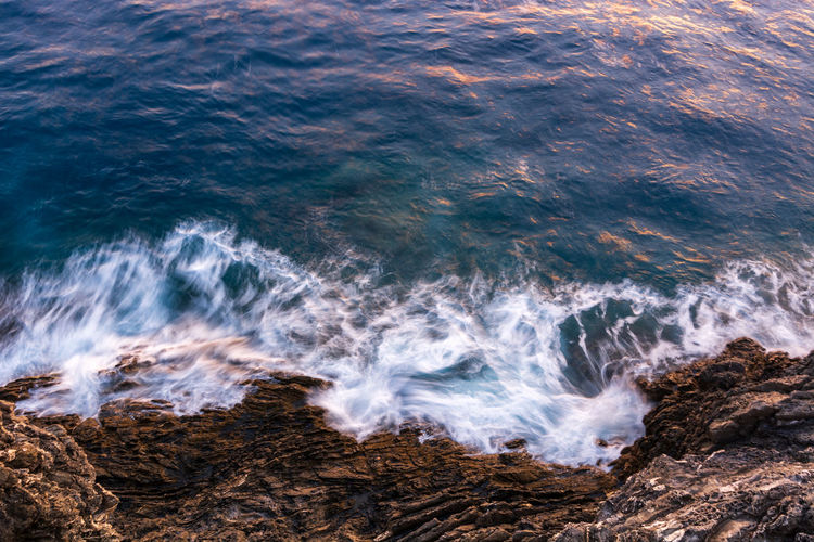 Aerial view of waves crashing at rocky shore