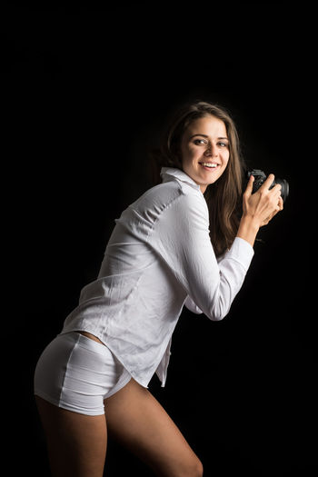 Three Quarter Length One Person Black Background Looking At Camera Portrait Smiling Happiness Studio Shot Women Young Adult Young Women Indoors  Adult Emotion Clothing Lifestyles Long Hair Cut Out Hair Hairstyle Beautiful Woman