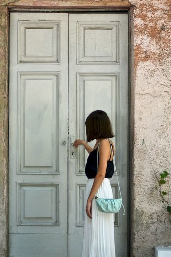 Side view of woman standing against closed door of building