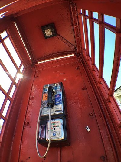 Low angle view of telephone booth on wall