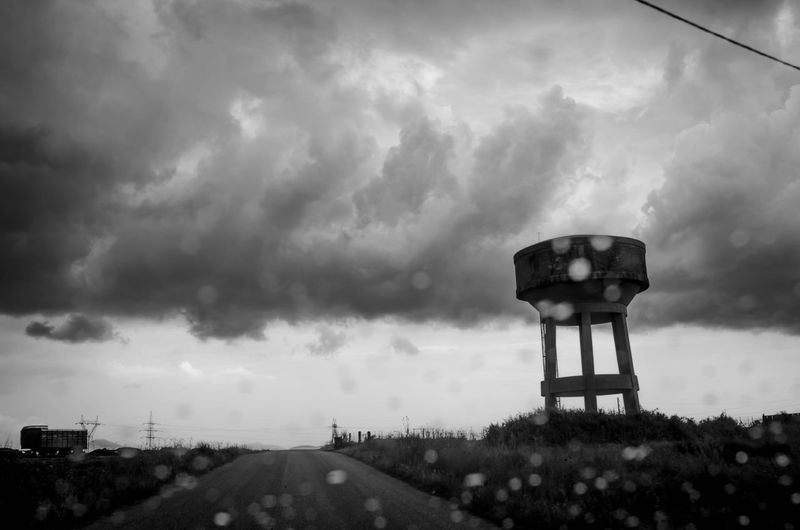 Water tower against cloudy sky seen through windshield