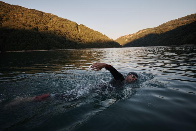 Man swimming in lake against sky