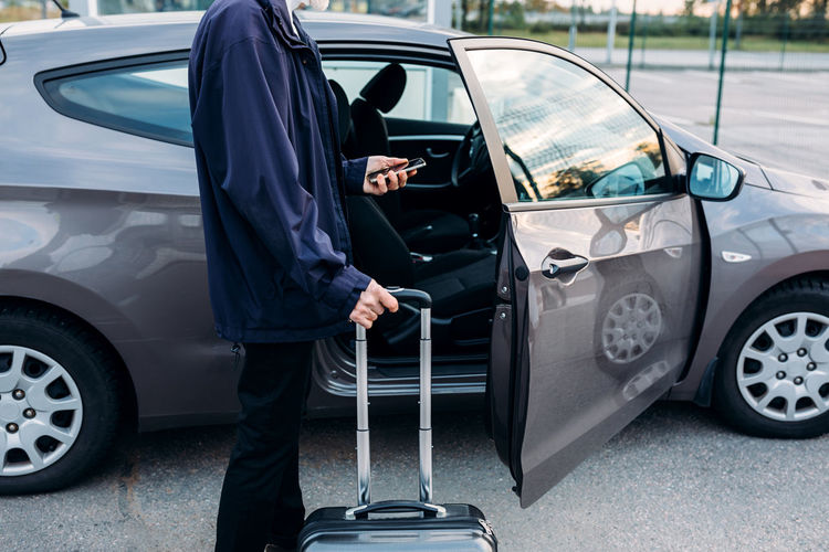 Man standing with luggage by car parked in city