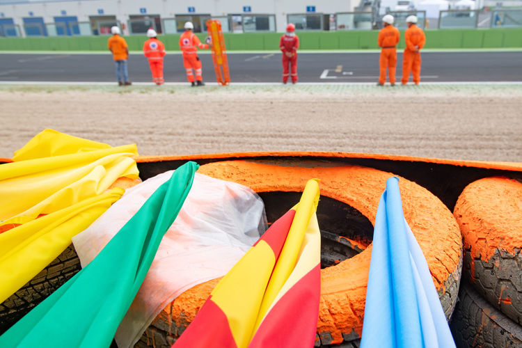 Warning flags on racing circuit barrier, people in background Asphalt Racing Day Flag Focus On Foreground Group Of People Multi Colored Outdoors Racing Circuit Racing Equipment Racing Flag Racing Track Real People Safety Safety Team Warning Flag Warning Sign