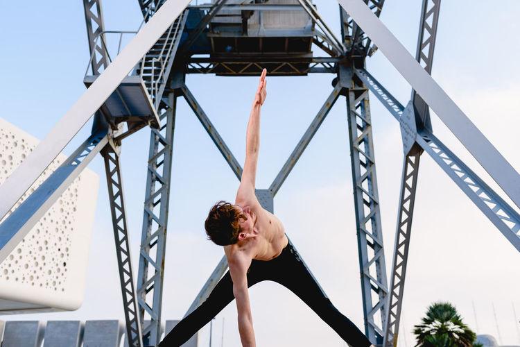 Shirtless man exercising against metallic structure