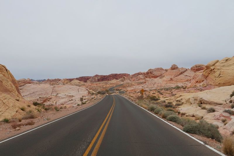 Road leading through multi colored hills in the desert