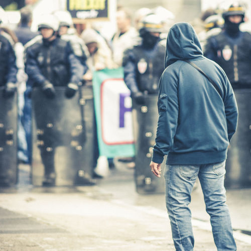Rear view of people walking on street in city du ring a riot with police