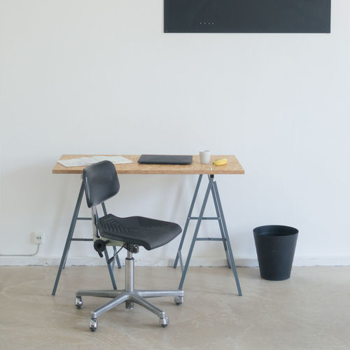 Chair by table against wall