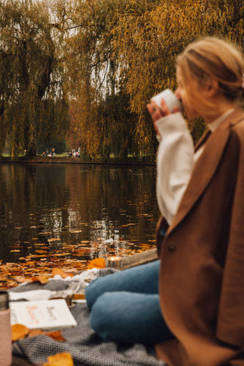 Woman sitting by lake during autumn
