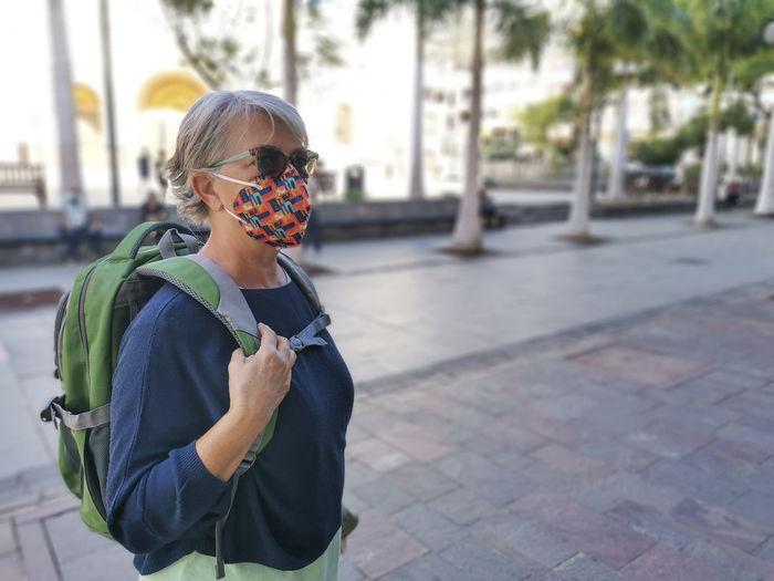 Senior woman wearing mask standing on footpath