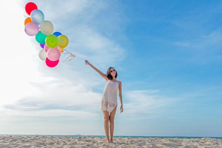 Full length of woman standing on balloons against sky