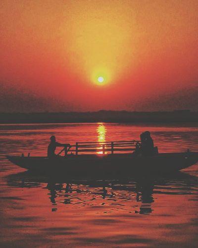 Silhouette people in sea against orange sky