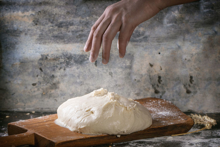 Man's hand powdered with flour the dough for pizza on wooden cutting board over dark kitchen table Action Bakery Baking Bread Bread Dark Photography Dough Flour Foodphotography Fresh Baked Hand Homemade Homemade Bread Human Body Part Human Hand Kitchen Kneading Making Preparation  Table
