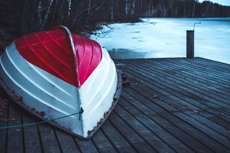 Umbrella on wooden pier in lake during winter