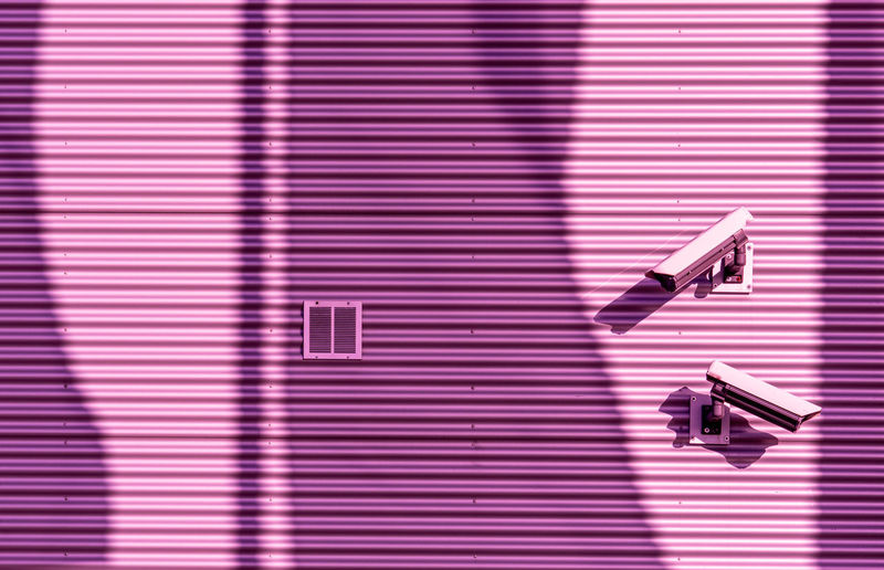 Low angle view of security cameras on pink wall