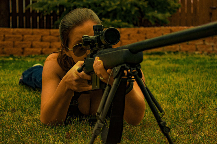 Mid Adult Woman With Sniper On Grassy Field