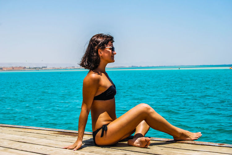 Side view of bikini woman sitting on pier over sea against clear sky