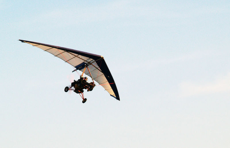 Low angle view of person hang-gliding against clear sky