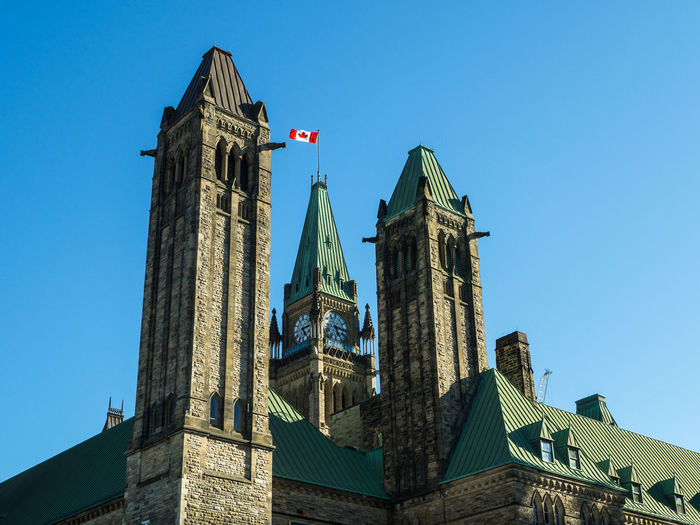 The Centre Block and the Peace Tower, Parliament of Canada in the beautiful day Architecture Built Structure Building Exterior Sky No People Building Nature Outdoors Low Angle View Day Tower Clear Sky The Past Blue History Travel Destinations Flag Travel Patriotism Blue Sky Springtime Spring Ottawa Canada City Cityscape Icon Symbol Democracy Politics And Government Politics Historic Historical Building Colors Parliament Building Red Sunlight Daylight