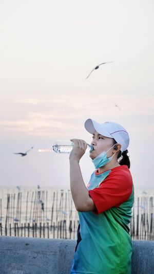 Side view of woman drinking water against sky