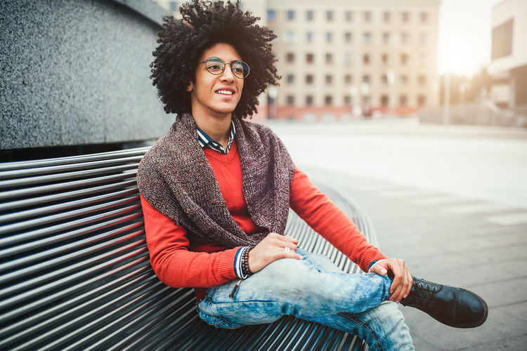 Smiling Young Man With Afro Hairstyle Sitting In City