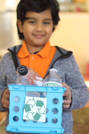 Boy holding crate with recycling symbol at home