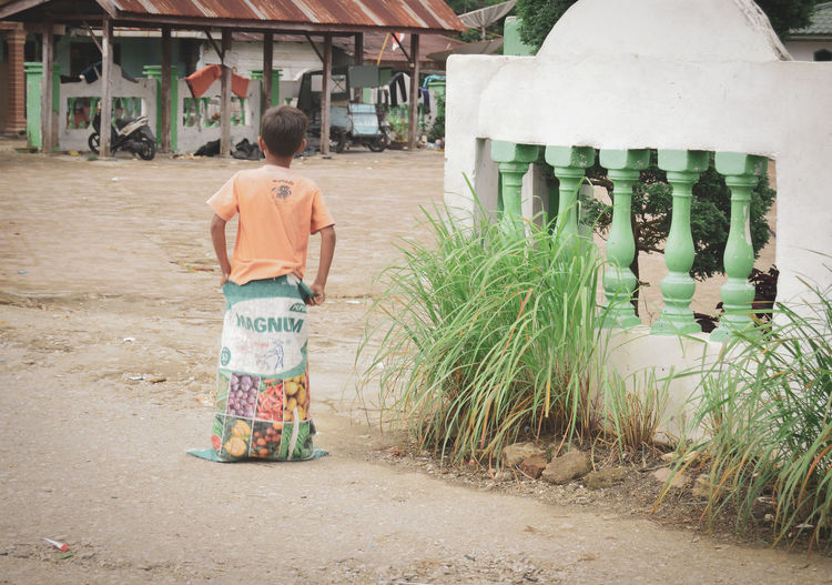 Rear view of boy walking outdoors