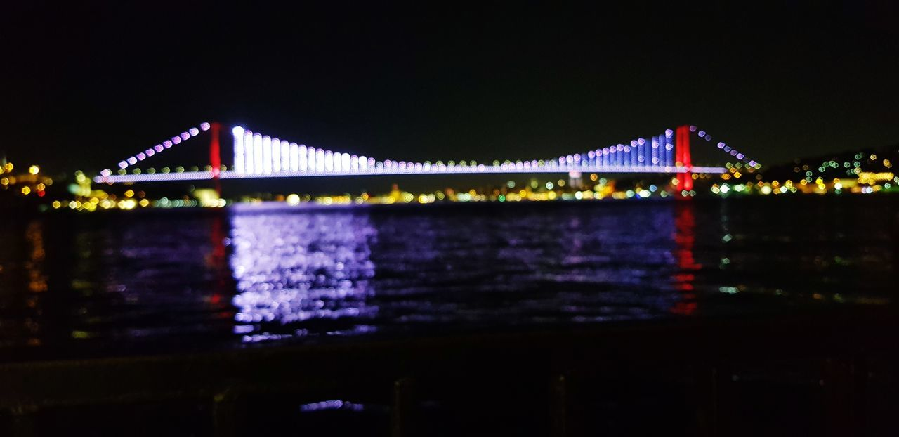 illuminated, night, water, built structure, bridge, reflection, river, architecture, connection, sky, bridge - man made structure, waterfront, no people, multi colored, nature, transportation, copy space, city, outdoors, light, nightlife