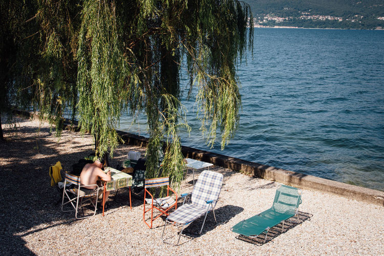 High angle view of shirtless senior man sitting at table by sea