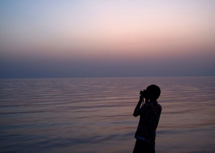 Silhouette of woman looking at sea