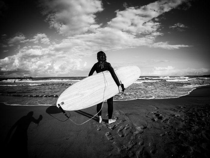Man with surfboard on beach against sky