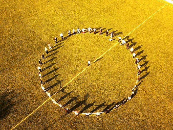 High Angle View Of People Forming Circle On Field During Sunny Day
