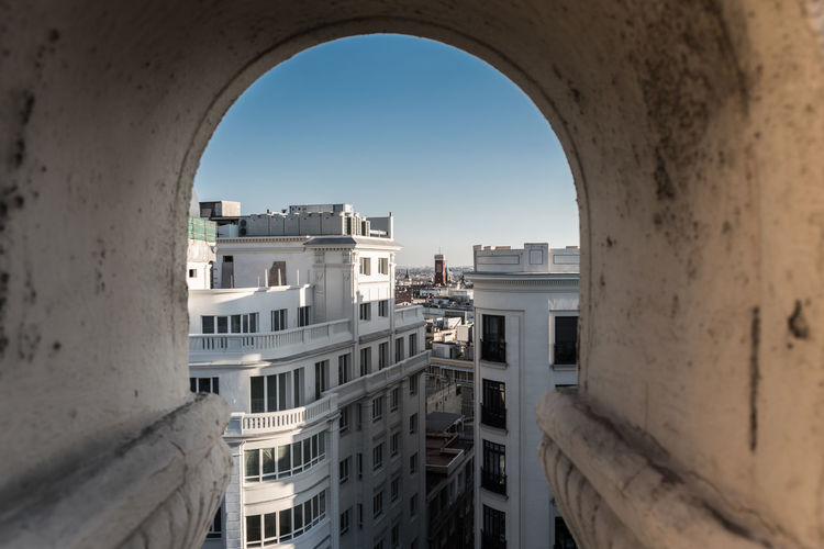 Buildings in city against clear sky seen through arch