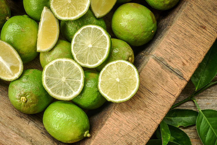 Fresh green lime with some slices and cut pieces on wooden tray background. Farm Natural Beauty Citrus Fruit Close-up Cross Section Food Food And Drink Food Ingredients Freshness Fruit Garden Green Color Healthy Eating Juicy Fruit Kitchen Lemon Lime Organic Peel Seasoning SLICE Sour Taste Thai Cooking Vitamin C Wood - Material