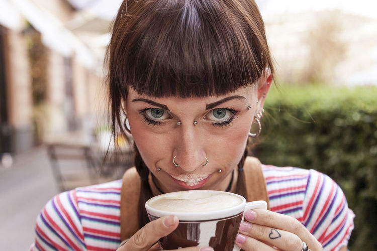 Portrait of young woman drinking coffee at outdoor cafe