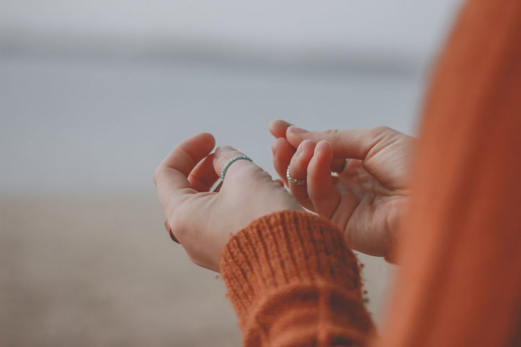 Close-up of woman wearing finger rings at beach