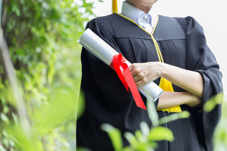 Midsection of young woman in graduation gown with arms crossed standing in park