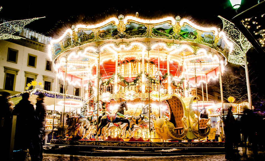 Illuminated carousel in amusement park at night