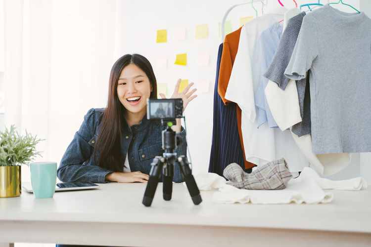 Portrait of young Asian woman recording a video for a woman fashion blogger. Asian  Asian Girl Woman Female Girl Young Women Young Adult Thailand Japanese  Korean Taiwanese Taiwan Beauty Beautiful Beautiful Woman Cute Relaxing Women Lady Portrait Blog Blogger Blogging Youtuber Sale Camera Recording Record One Person Smiling Table Front View Happiness Real People Indoors  Casual Clothing Looking At Camera Emotion Leisure Activity Clothing Furniture Adult Hairstyle Cloth Clothes