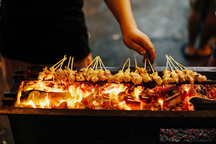 Midsection of man preparing satay on barbecue