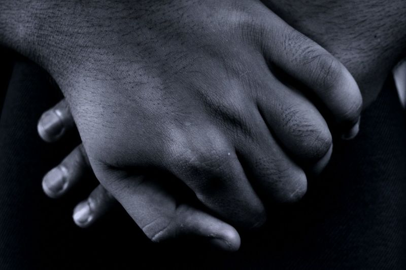 Cropped image of person with hands clasped