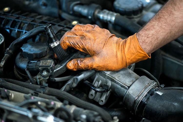 Cropped hands of male mechanic repairing car at auto repair shop