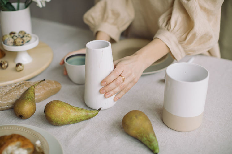 Midsection of woman with fruits having tea on table