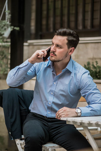 Businessman talking on mobile phone while sitting on table outdoors