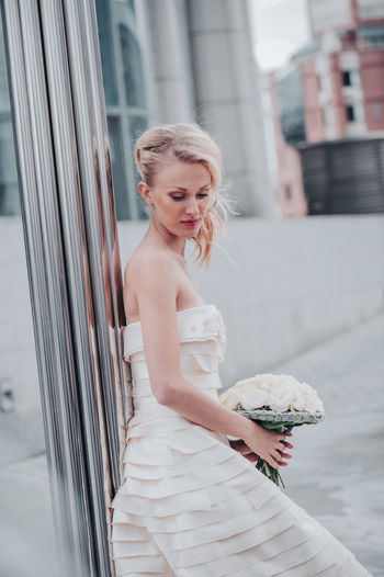 Beautiful bride with bouquet against wall in city
