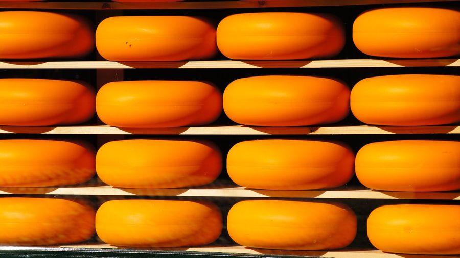 Rows of yellow gouda cheese on shelf
