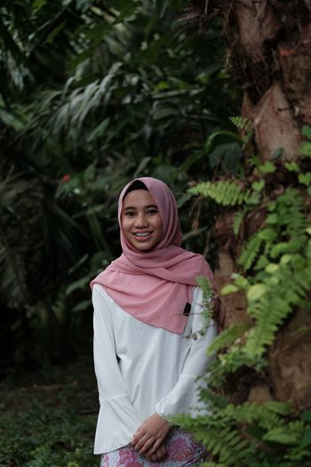 Portrait of smiling teenage girl wearing hijab standing at public park