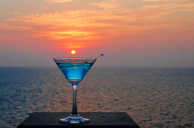 Close-Up Of Martini Glass Against Sea During Sunset